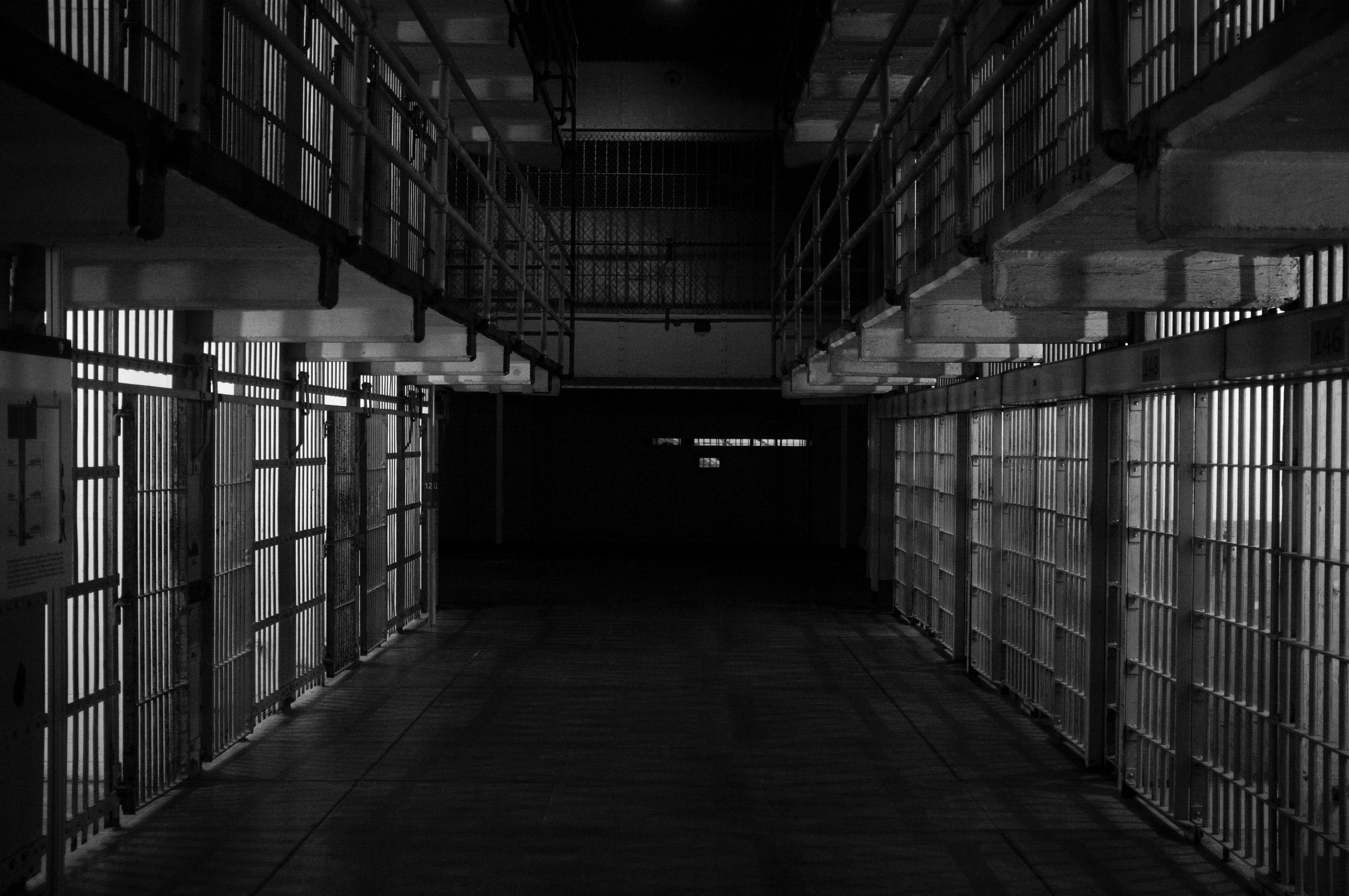 Row of jail cells; image by Emiliano Bar, via Unsplash.com.