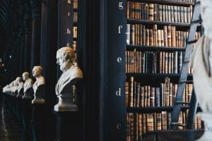 Library shelves with busts of famous people; image by Giammarco Boscaro, via Unsplash.com.
