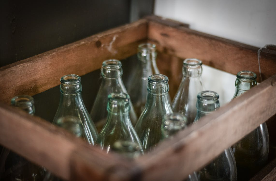 A wooden crate holding empty, clear glass bottles.