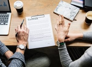 Two people reviewing a contract; image by Rawpixel, via Unsplash.com.