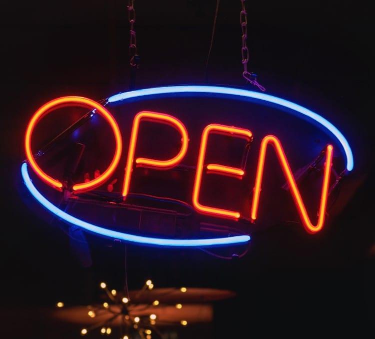 """Orange """"Open"""" neon sign; image by Tom Mossholder, via Unsplash.com."""