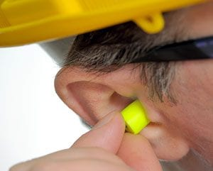 Man Inserting Earplugs