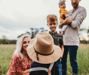Man and woman with three children in a field; image by Jessica Rockowitz, via unsplash.com.