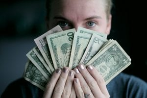 Woman holding money in front of her face; image by Sharon McCutcheon, via unsplash.com.