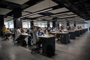 Large group of people working on computers at desks in rows; image by Alex Kotliarskyi, via Unsplash.com.
