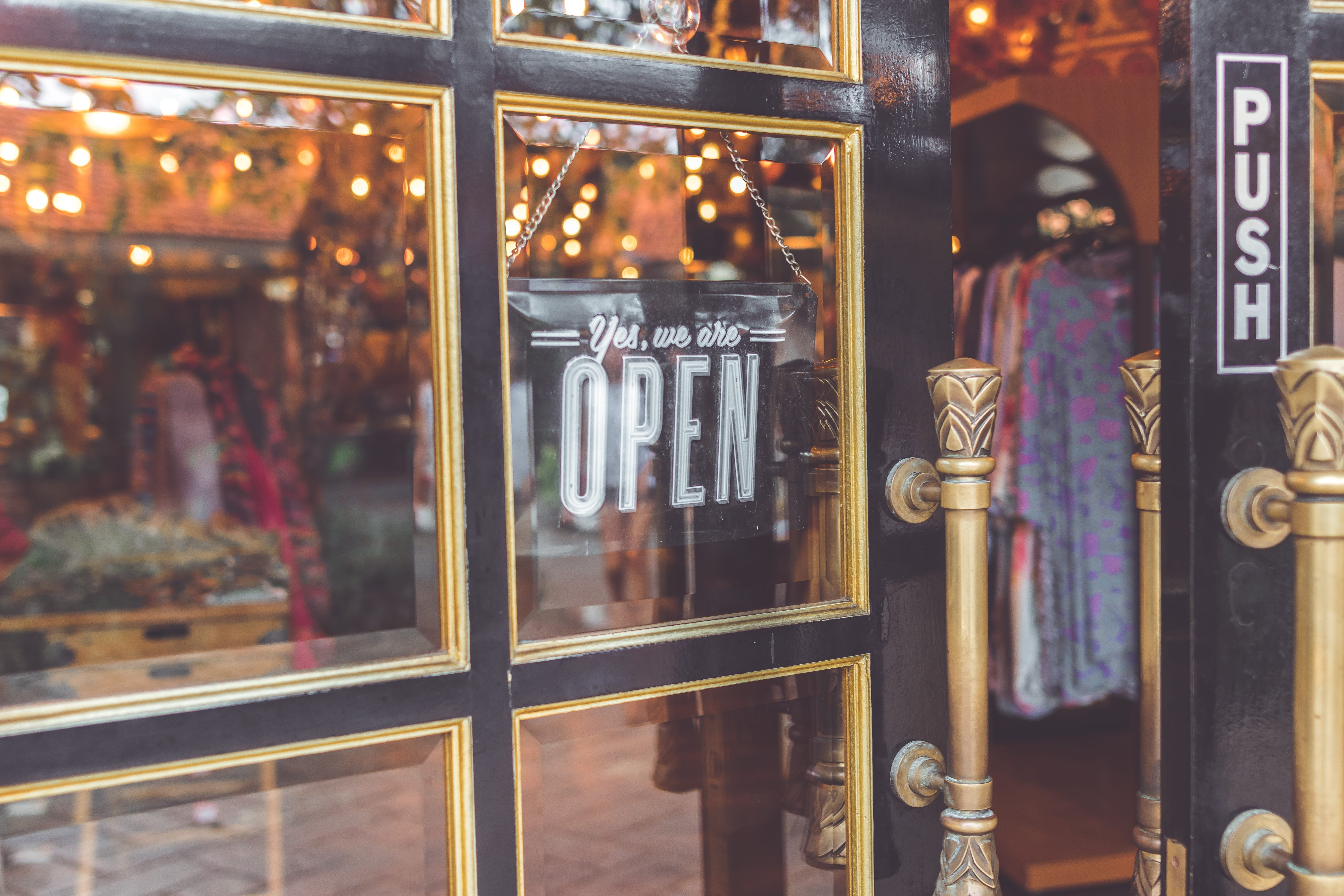 """Shopfront with sign in window saying """"Yes, We Are Open;"""" image by Artem Bali, via unsplash.com."""