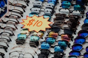 """Assorted eyeglasses and sunglasses with sign reading """"$10""""; image by Chutterstock, via Unsplash.com."""