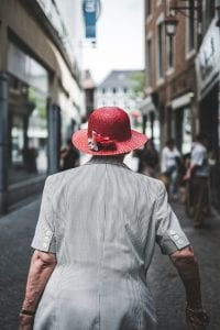 Woman in gray dress and red hat walking away; image by Fabio Neo Amato, via Unsplash.com.