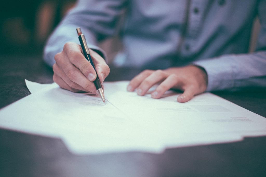 Man in blue shirt writing a document; image by Helloquence, via unsplash.com.