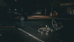 Bicycle in the middle of the street at night with black van nearby; image by Ian Valerio, via Unsplash.com.