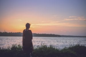 Woman looking at body of water at sunset; image by Praveesh Palakeel, via Unsplash.com.
