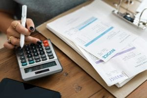 Woman holding a white pen using a calculator to run business figures; image by Rawpixel, via Unsplash.com.