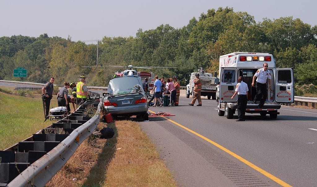 Car accident at side of road with emergency workers and ambulance; image by Ragesoss, via Wikimedia Commons, CC BY-SA 3.0, no changes.