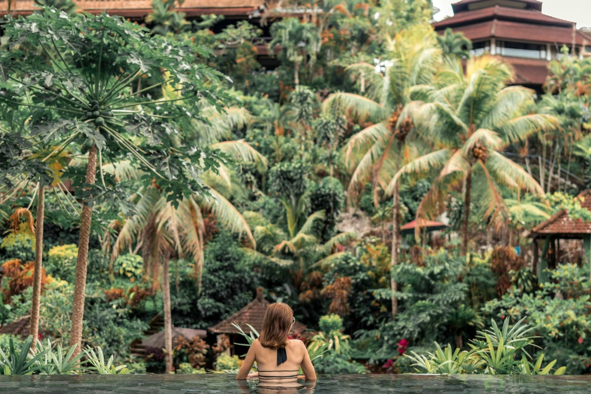 Woman in beautiful lagoon with her back to camera looking at lush jungle; image by Artem Bali, via unsplash.com.