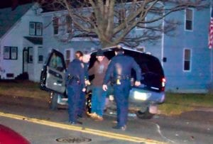 Three uniformed police officers surround a driver being given a sobriety test at night.