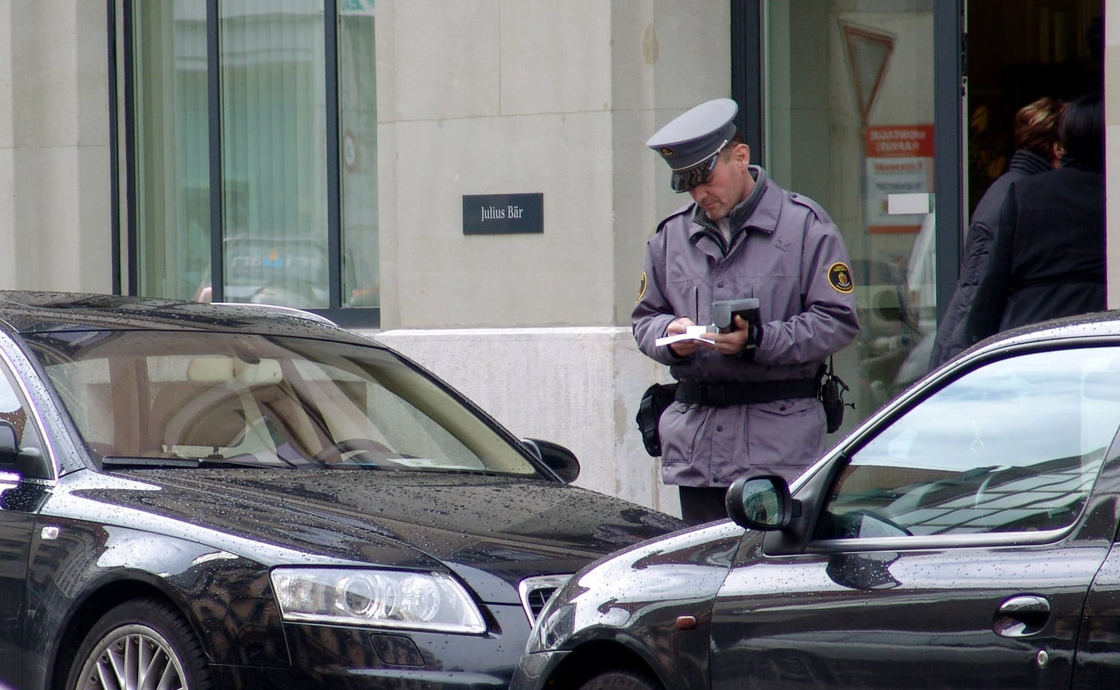 A policeman in uniform stands between two cars, writing a parking ticket.