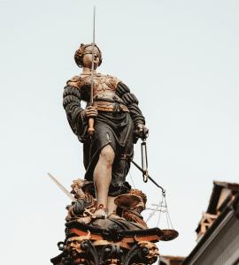 Statue of Lady Justice, blindfolded, holding sword and scale; image by Joel & Jasmin Førestbird, via unsplash.com.