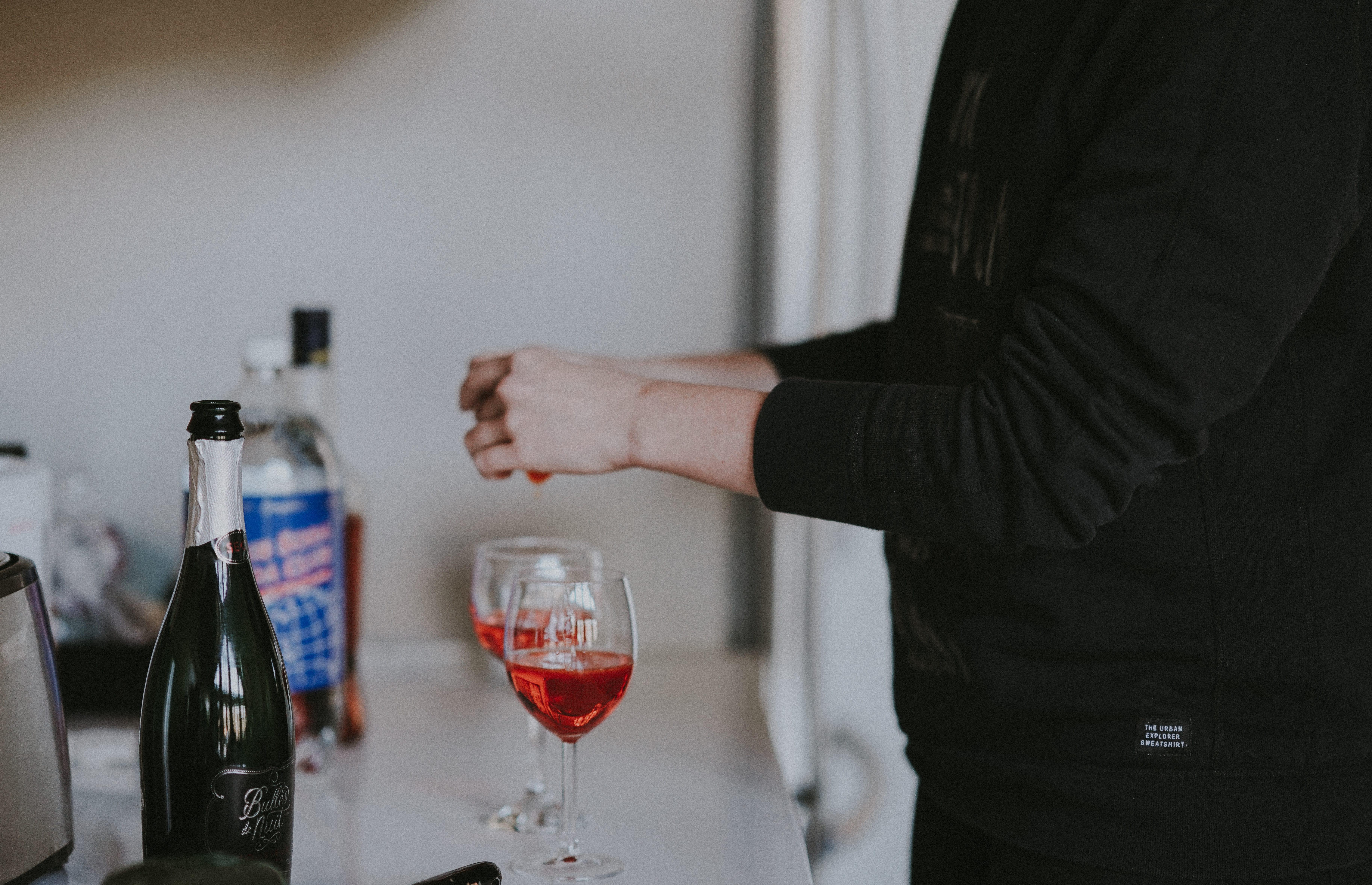 Woman making a cocktail; image by Annie Spratt, via Unsplash.com.
