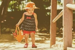 Little girl wearing red shorts, black top, and straw hat walking; image by Miguel R. Perez, via Pixabay.com.