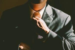 Man in suit loosening tie; image by Ben Rosett, via unsplash.com.