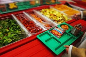 A young person carrying a tray chooses among many brightly colored fruit and vegetable options in a cafeteria setting.