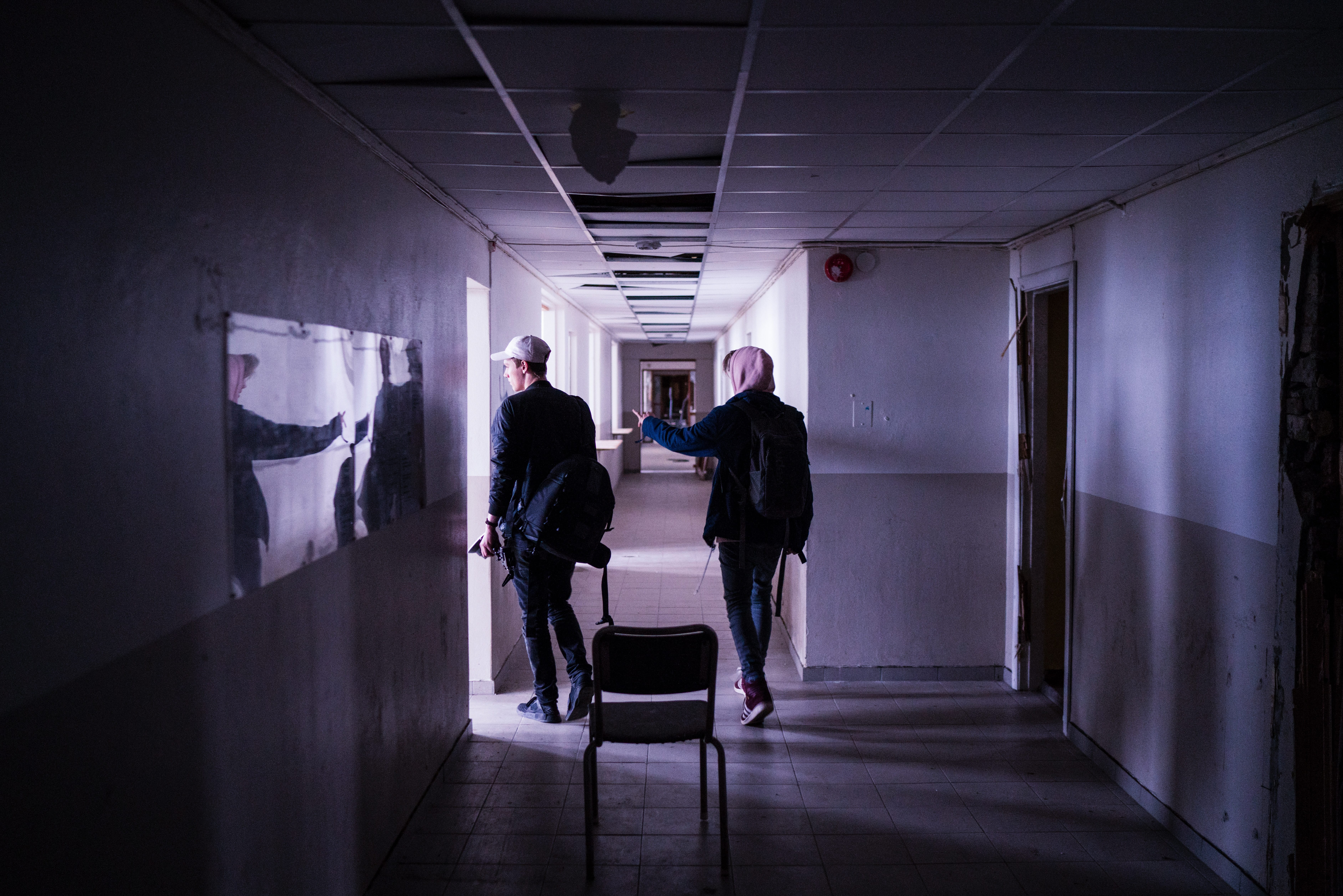 Two men walking down a hallway; image by Daniel Tafjord, via unsplash.com.