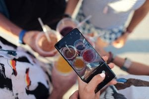 Person taking a picture of mixed drinks; image by David Calderón, via Unsplash.com.