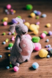 Stuffed rabbit holding a stuffed Easter egg surrounded by colored cotton balls; image by freestocks.org, via Unsplash.com.