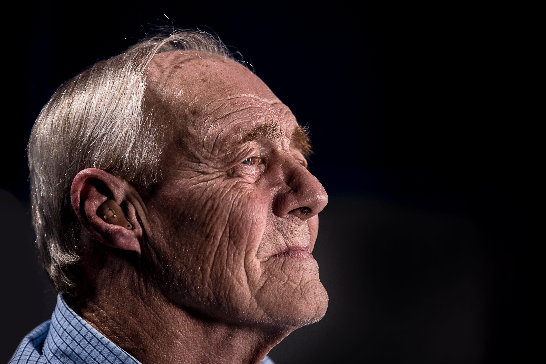 Older man wearing a hearing aid; image by JD Mason, via Unsplash.com.