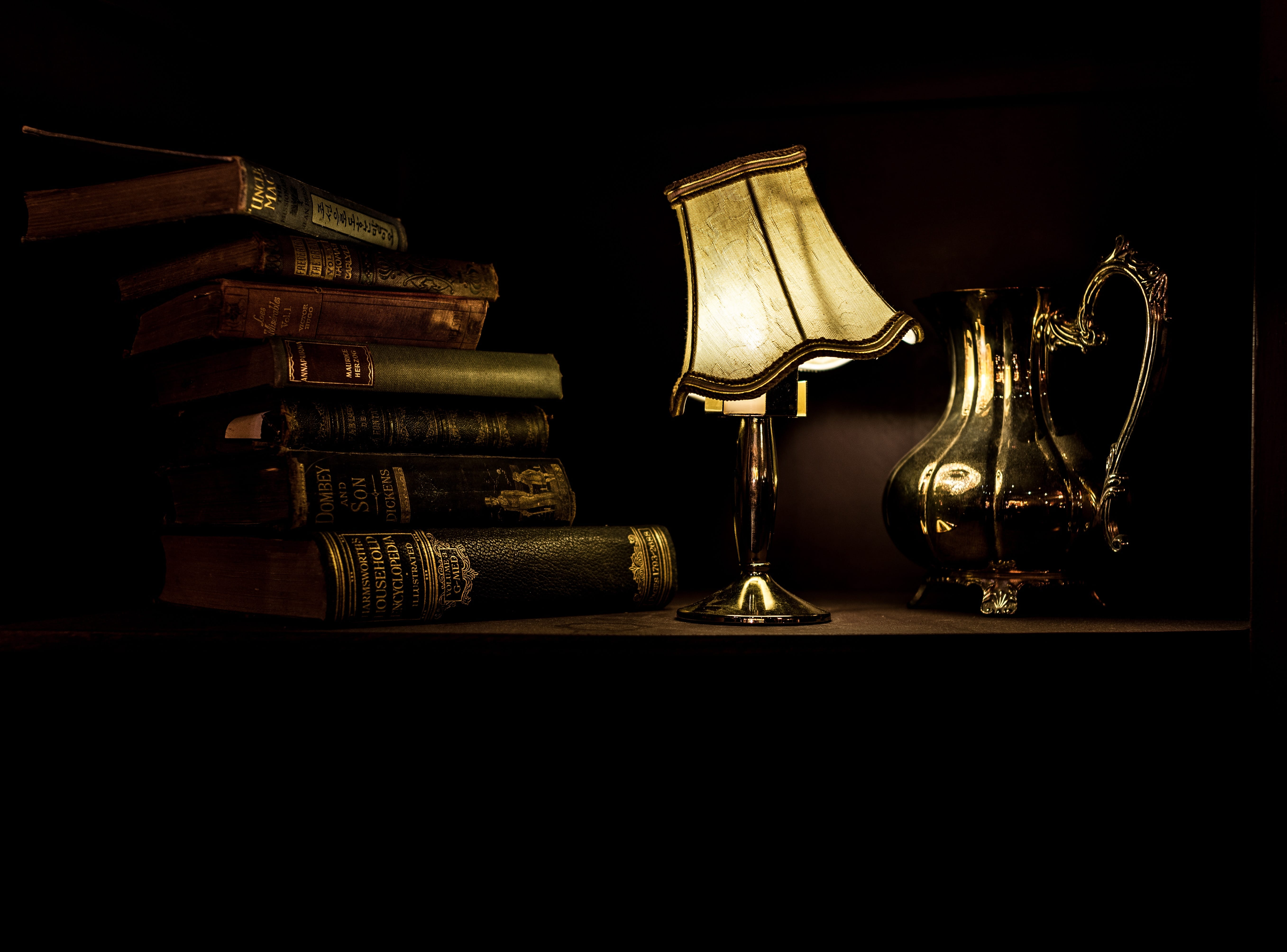 Books on a desk with a lamp and pitcher; image by Jez Timms, via Unsplash.com.