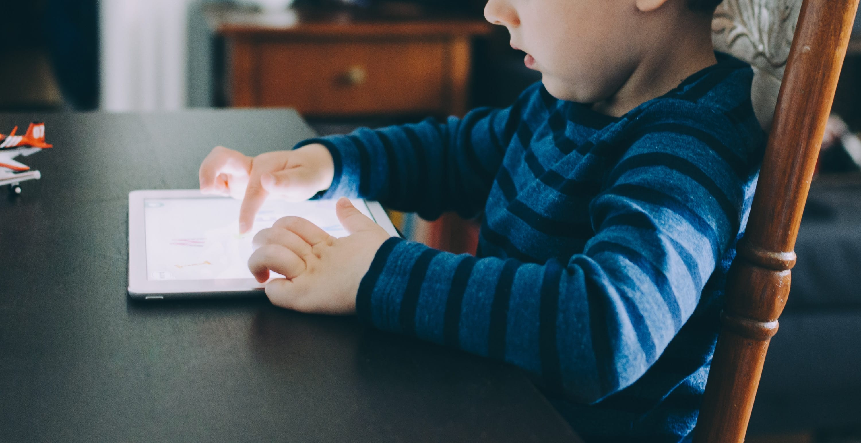 Young boy sitting at a table using a tablet computer; image by Kelly Sikkema, via unsplash.com.