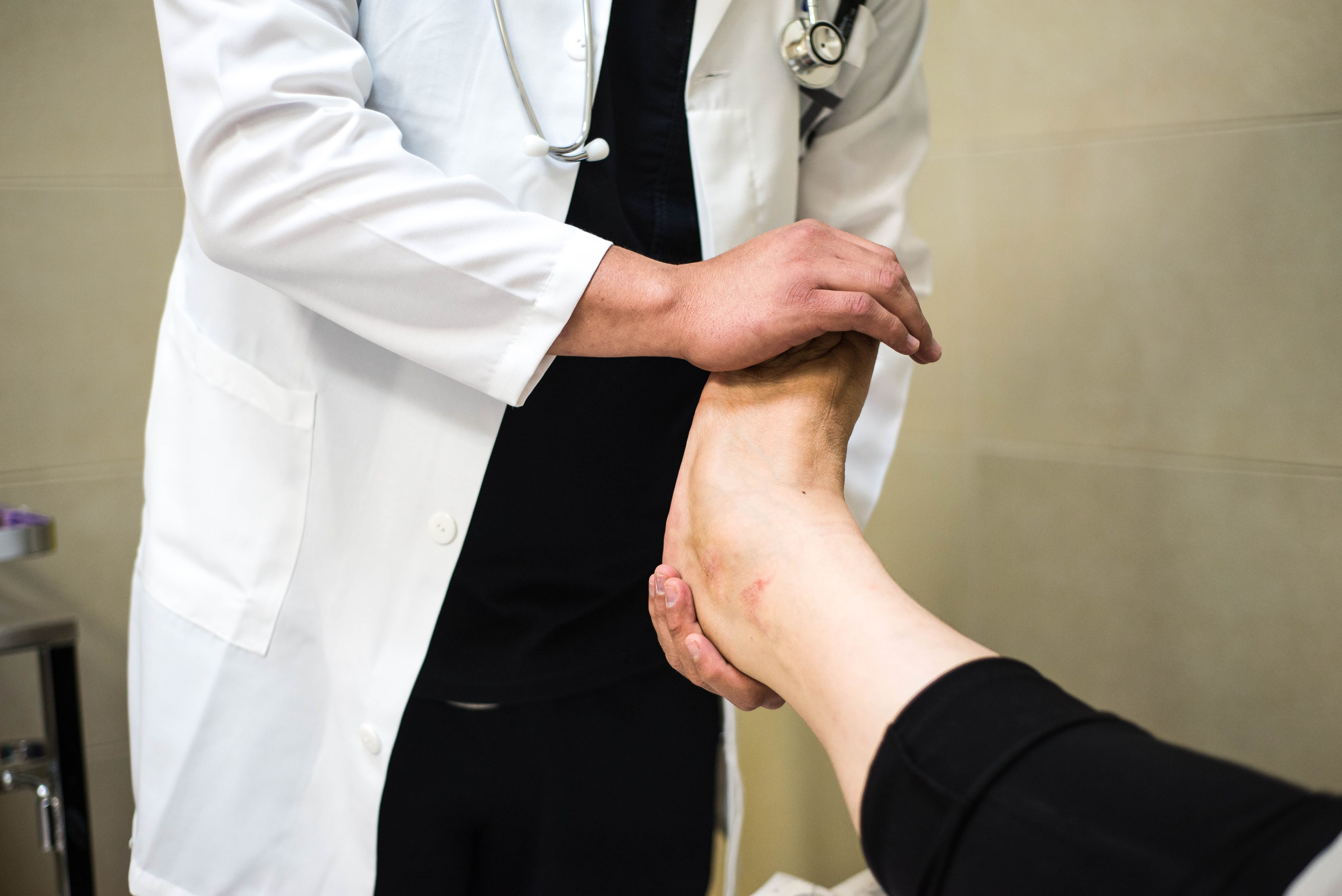 Doctor holding patient's foot; image by Marlon Lara, via unsplash.com.