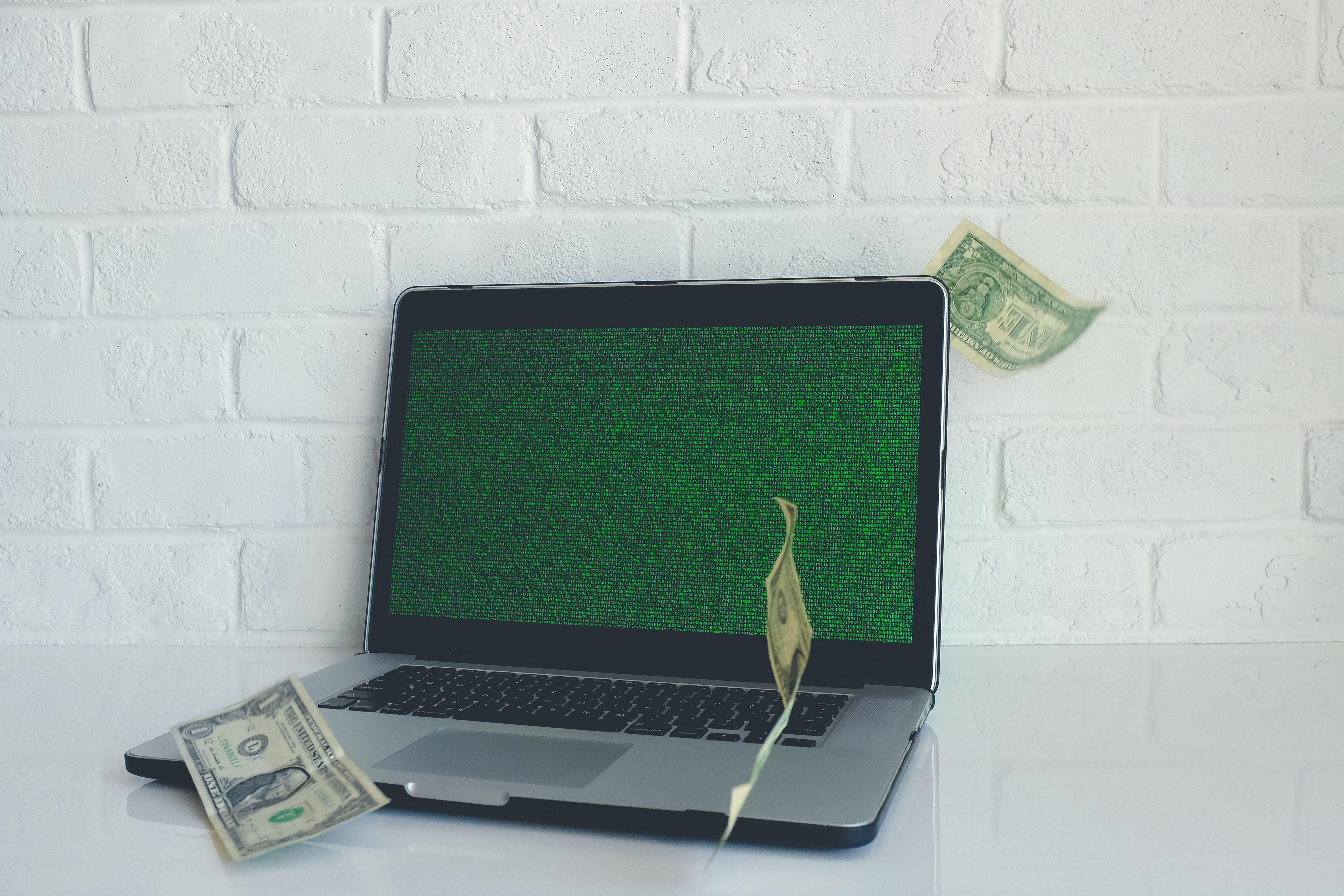 Laptop with green screen and money falling from above; image by NeONBRAND, via unsplash.com.