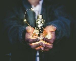 Man holding lit up light bulb; image by Riccardo Annandale, via unsplash.com.