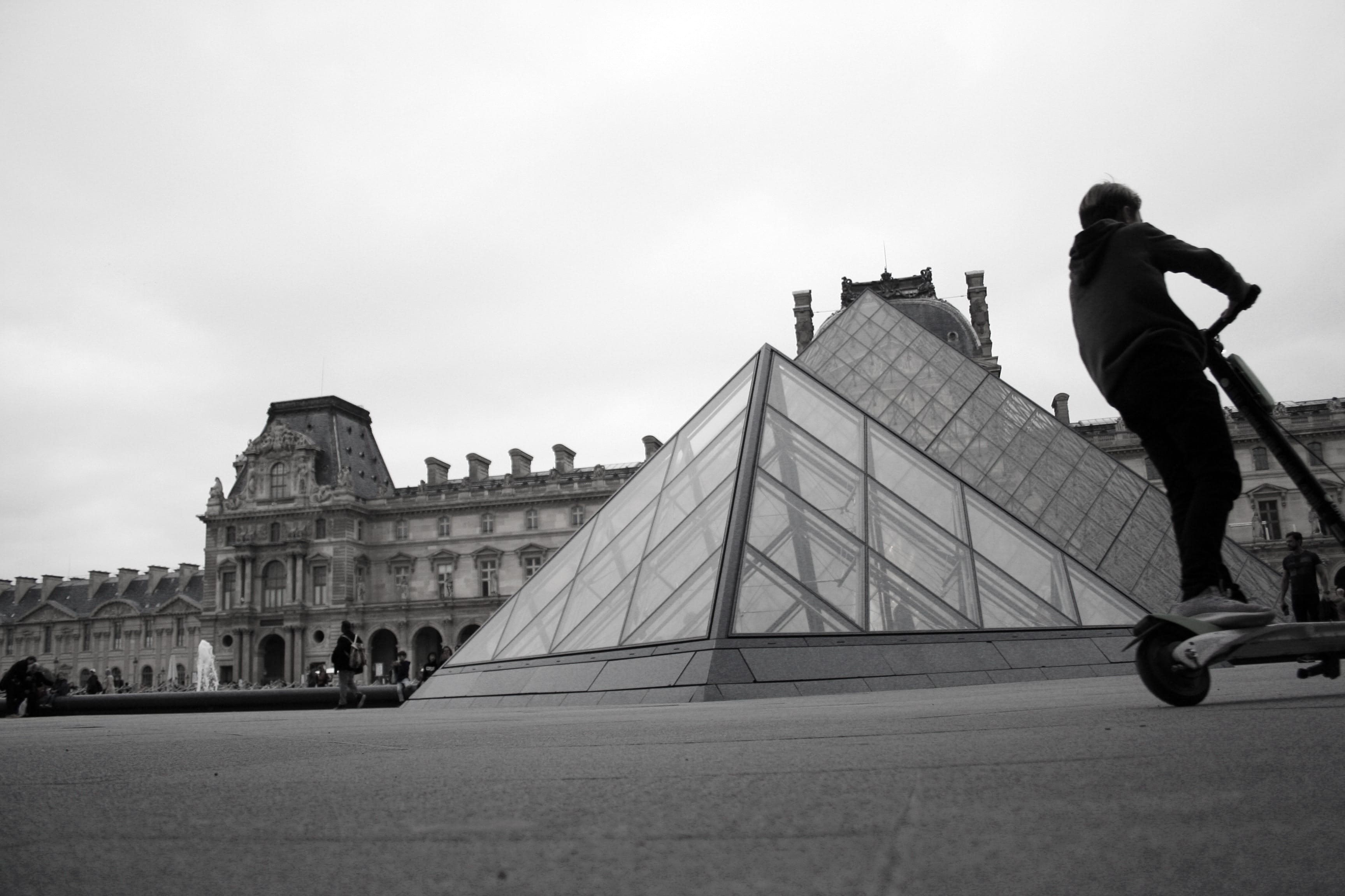 Man riding a Lime electric scooter outside the Louvre in Paris, France; image by Timothy K, via unsplash.com.