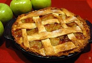 A golden brown lattice-crusted apple pie, with four green apples sitting nearby.