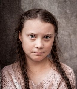 A serious-looking teenage girl with braided hair, wearing a pale colored sweater against a dappled grey background wall.
