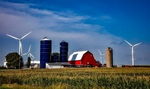 A classic red barn, surrounded by agricultural fields, silos, and wind turbines.