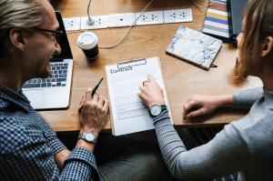 A man and a woman reviewing a contract at a desk; image by Rawpixel, via Unsplash.com.