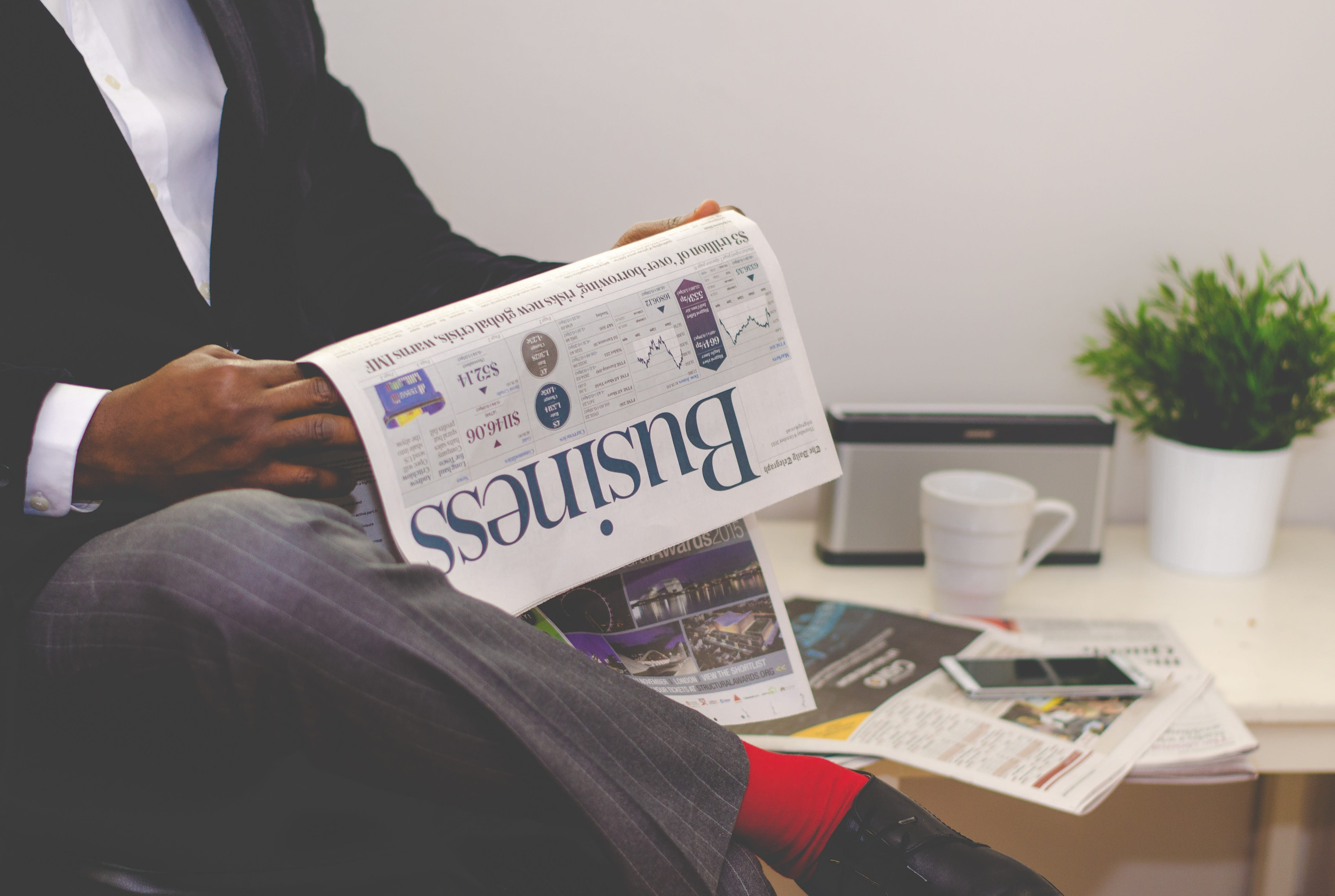 Man reading the Business section of the newspaper while having coffee at a table; image by Adeolu Eletu, via unsplash.com.