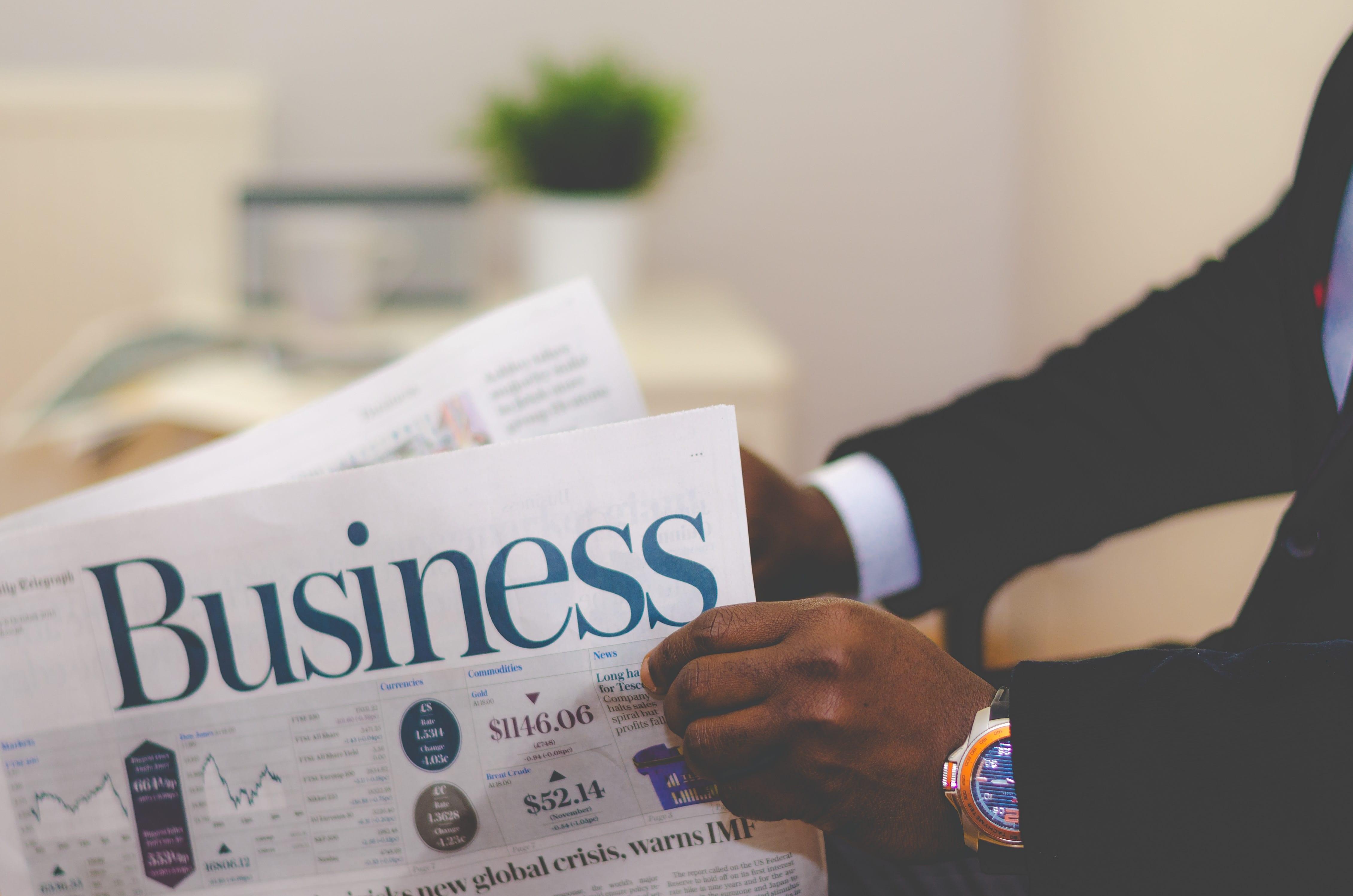 Man in suit reading business newspaper; image by Adeolu Eletu, via Unsplash.com.