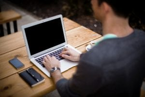Man seated at an outdoor table working on a laptop; image by Alejandro Escamilla, via unsplash.com.