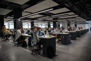 People working at various computer desks; image by Alex Kotliarskyi, via Unsplash.com.