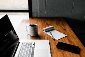 Laptop, smartphone, pad of paper and pen, and cup of coffee on a woodgrain table; image by Andrew Neil, via unsplash.com.