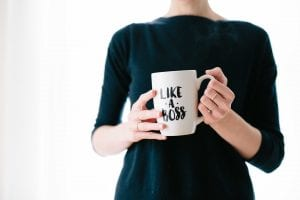 "Woman in black blouse holding a white coffee mug that reads ""Like a Boss;"" image by Brooke Lark, via Unsplash.com."