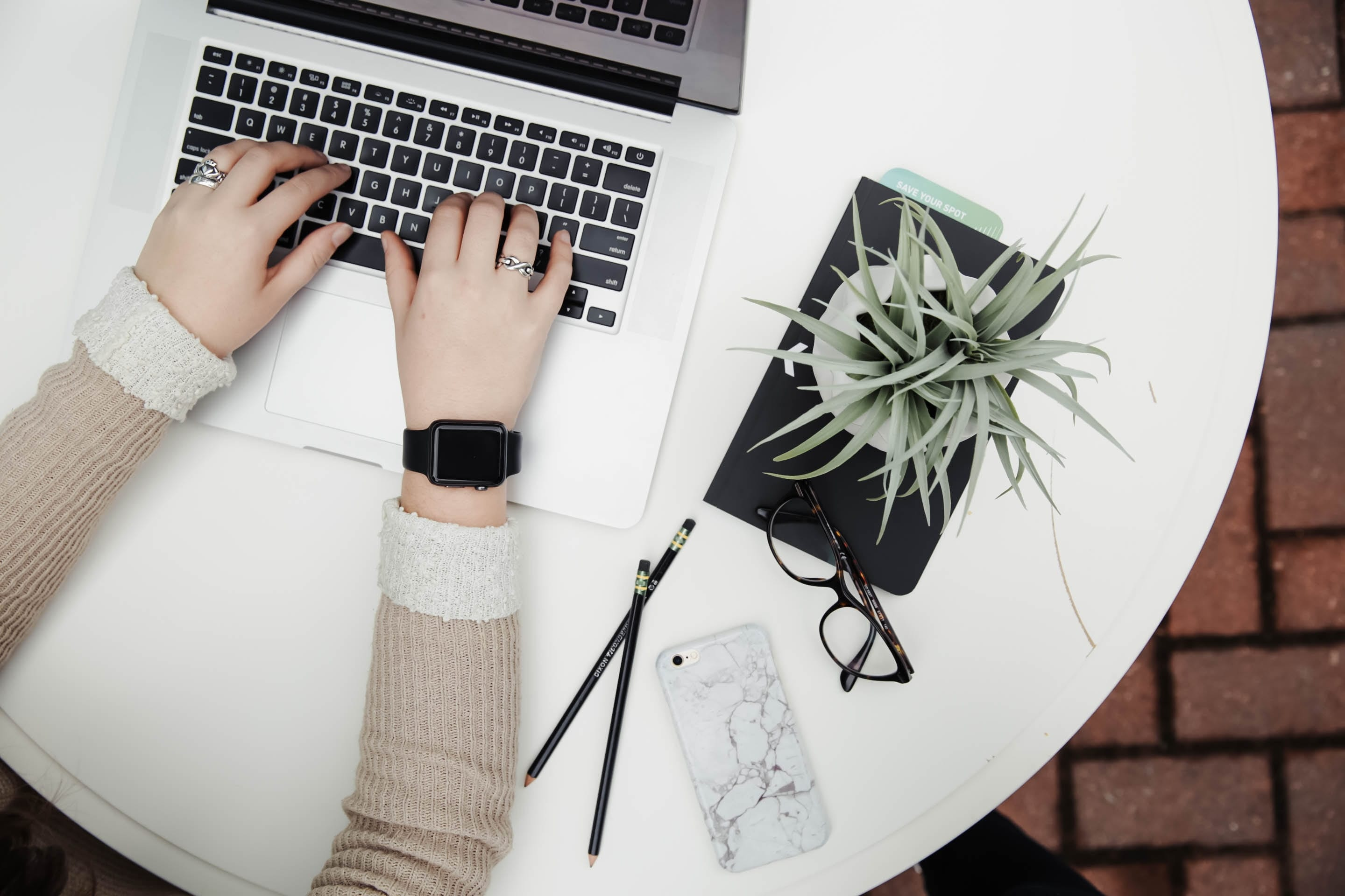 Woman at circular table working on a laptop with a plant, eyeglasses, smartphone and pencils nearby; image by Corinne Kutz; via Unsplash.com.