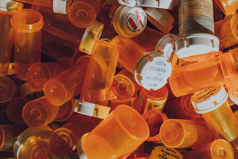 A pile of empty orange prescription bottles; image by Haley Lawrence, via unsplash.com.
