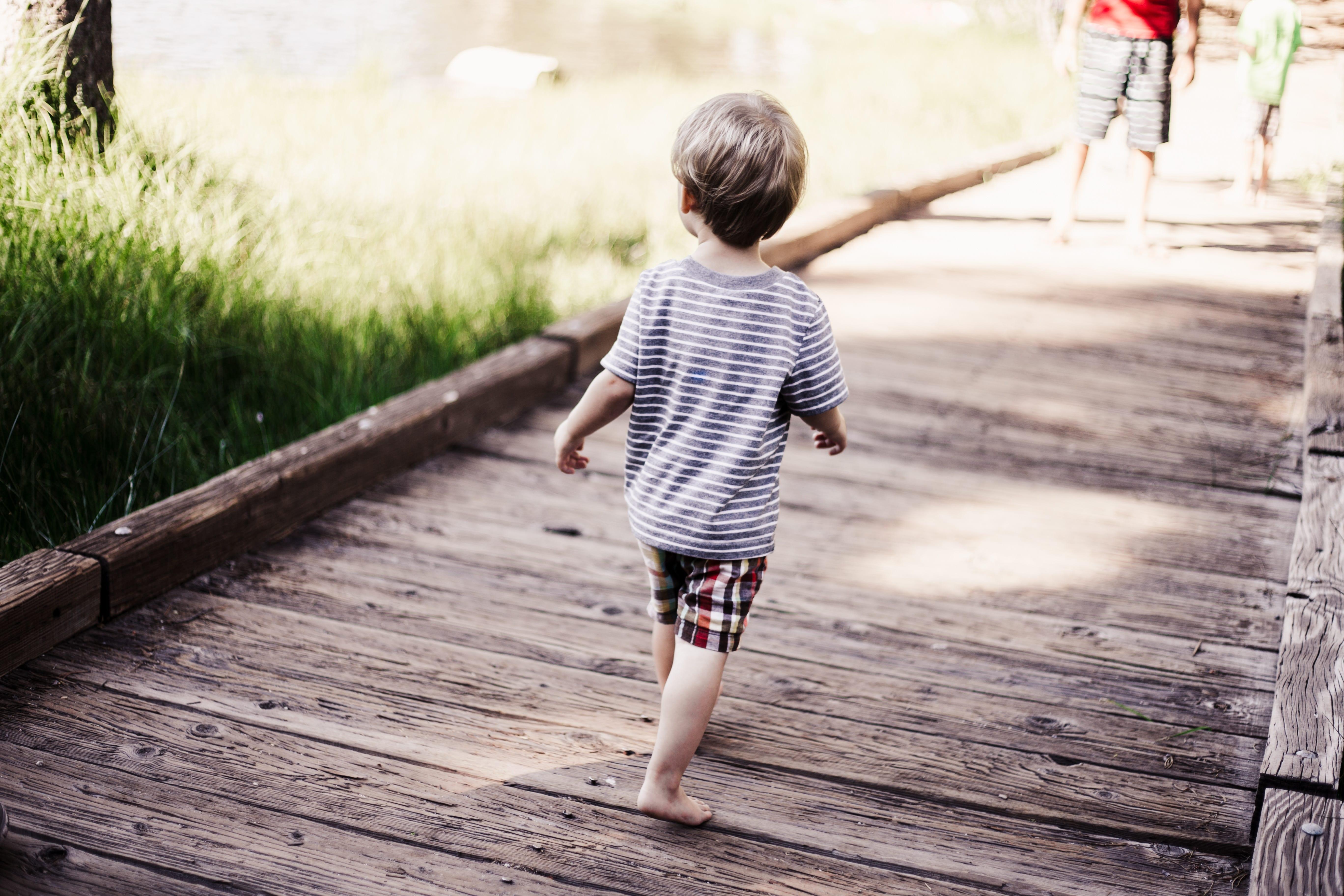 Young boy walking on bridge; image by Japhet Mast, via Unsplash.com.
