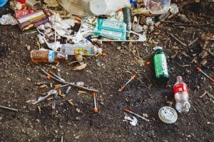 Used syringes, soda bottles, and assorted trash; image by Jonathan Gonzalez, via Unsplash.com.