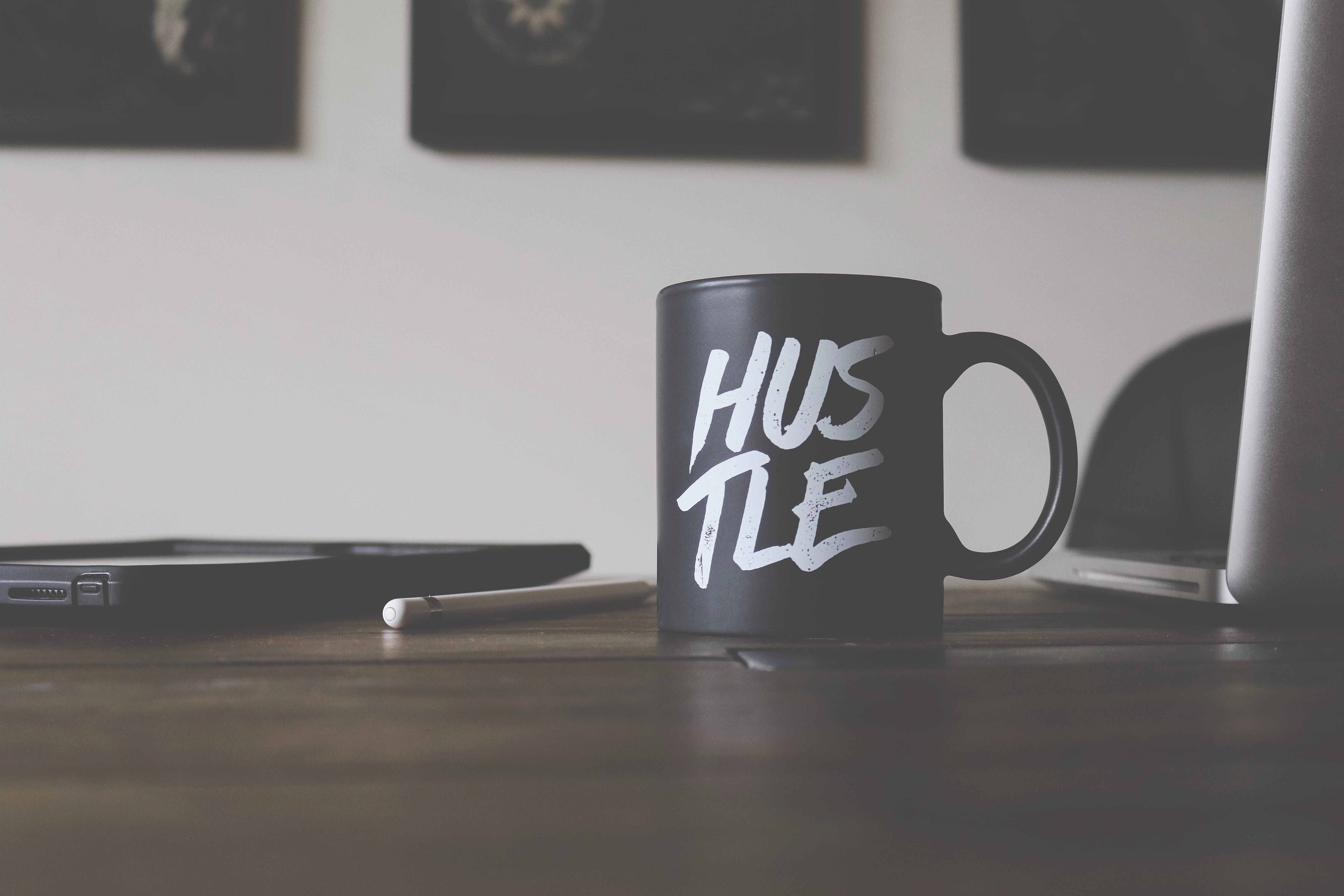 "Black mug with ""Hustle"" spelled in white letters on table with smartphone, laptop, and pen; image by Lost Co., via Unsplash.com."